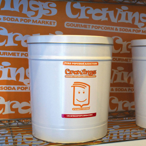 Craving's Popcorn tins with custom stickers, printed on adhesive vinyl. Background logo shelf-liner printed on 3mm white PVC.